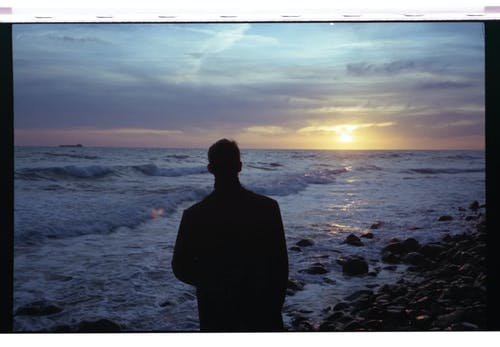 Silhouette of Man Standing on Rocky Shore during Sunset