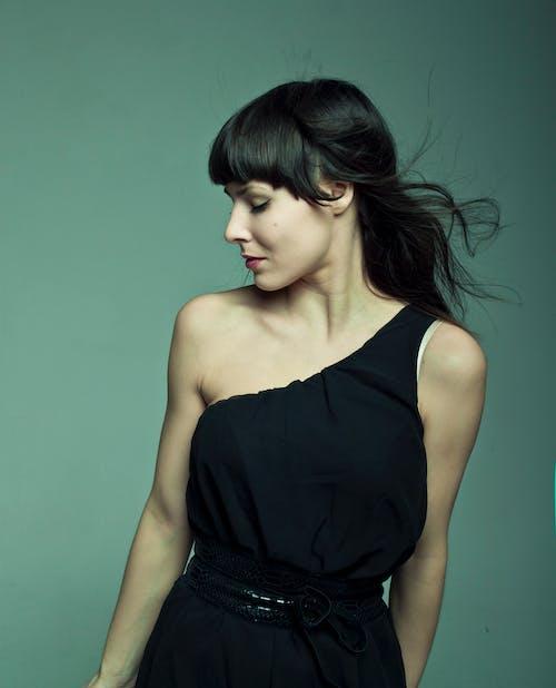 Elegant woman in dress with flying hair in studio