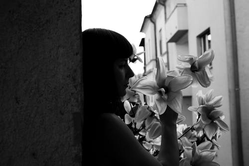 Upset woman smelling lily flower standing near concrete wall