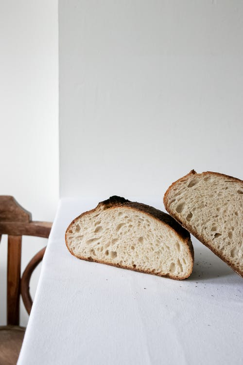 Delicious wholesome freshly baked bread cut in halves and arranged on white counter in light kitchen