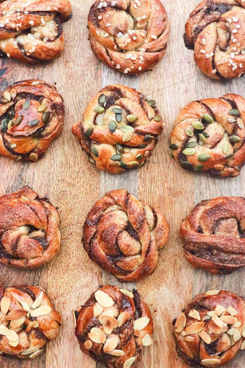 Sweet buns with grains arranged on wooden board