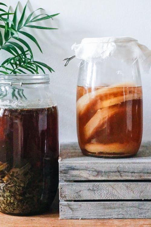 Jars with kombucha and dark herbal beverage