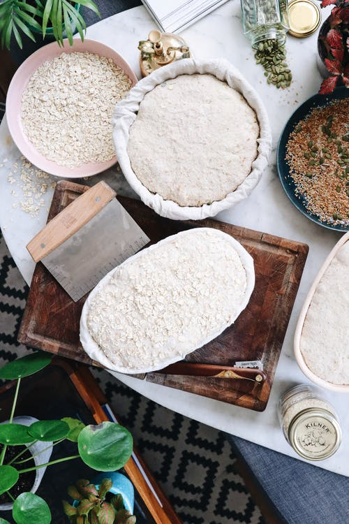 Top view of dough and ingredients prepared for baking bread on table in kitchen