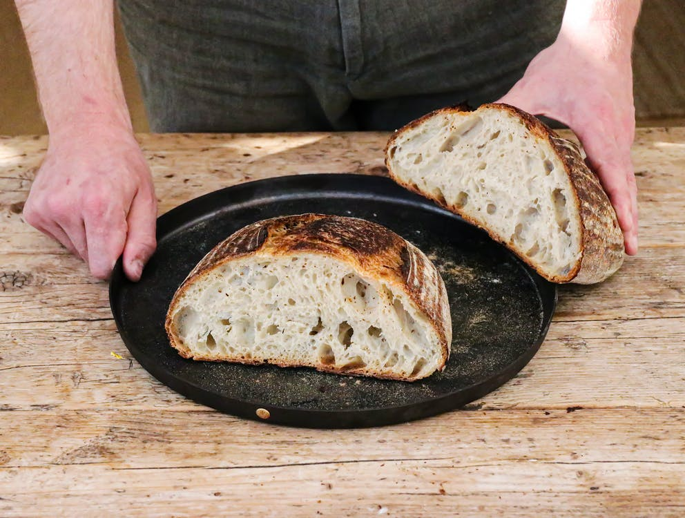 Baker with cut loaf on plate