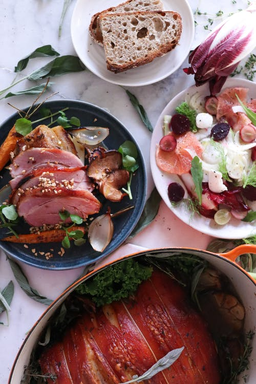 Top view of assorted palatable dish with grilled meat and bacon placed near meal with slices of meat and salad with vegetables on table with bread