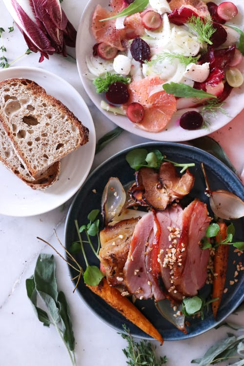 Top view of bowl with slices of meat with grilled vegetables and fruit placed on table near salad and bread