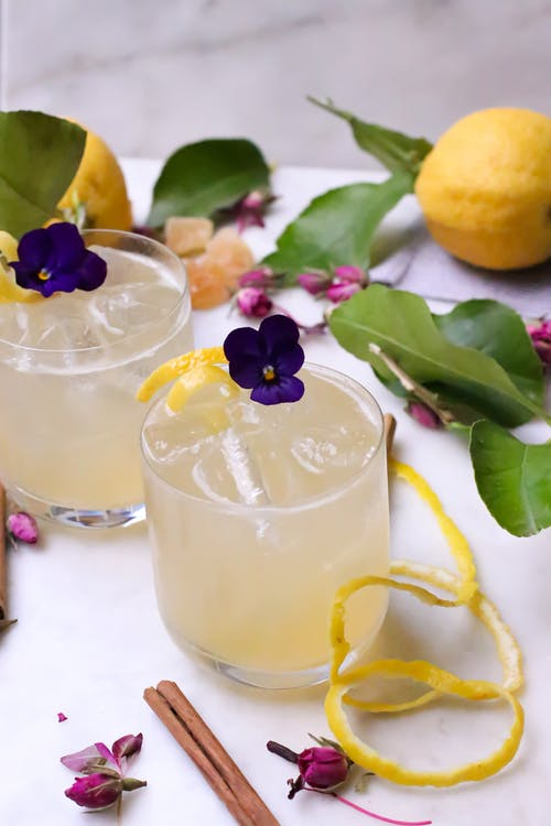 From above of transparent glasses with alcohol drinks and ice decorated with flowers and zest placed on table with ripe lemons and cinnamon