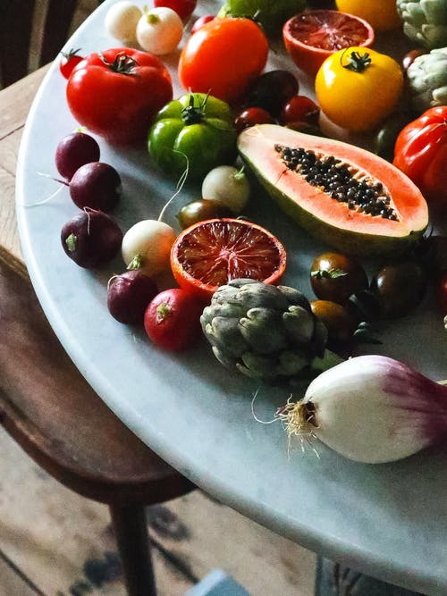 Bunch of various ripe exotic fruits and ripe healthy vegetables placed on marble table in light kitchen during harvest season