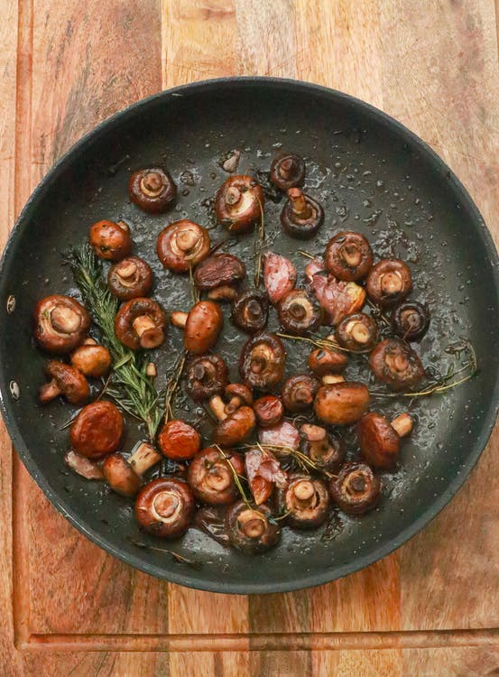 Top view of many little tasty mushrooms in frying pan with green rosemary and garlic placed on wooden table in kitchen