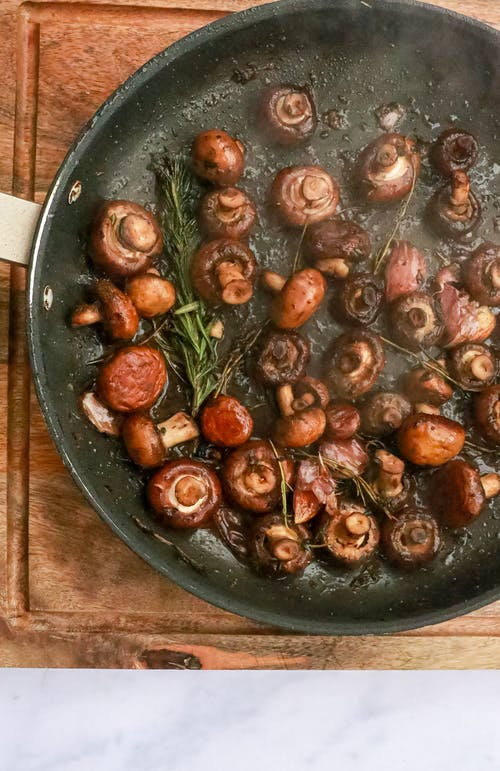Frying mushrooms with rosemary in pan