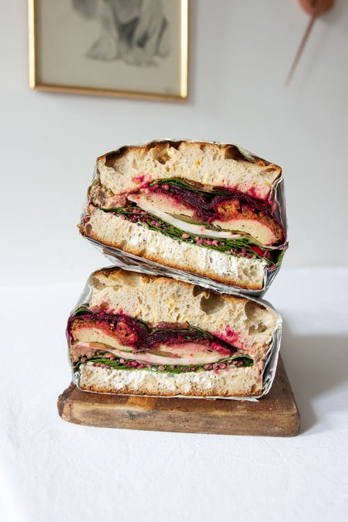 Appetizing sandwiches served on wooden board in restaurant