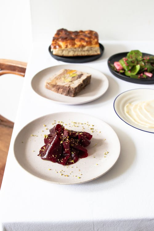 From above plates of beetroot dish and meatloaf served on white table with fresh salad and bread in light restaurant