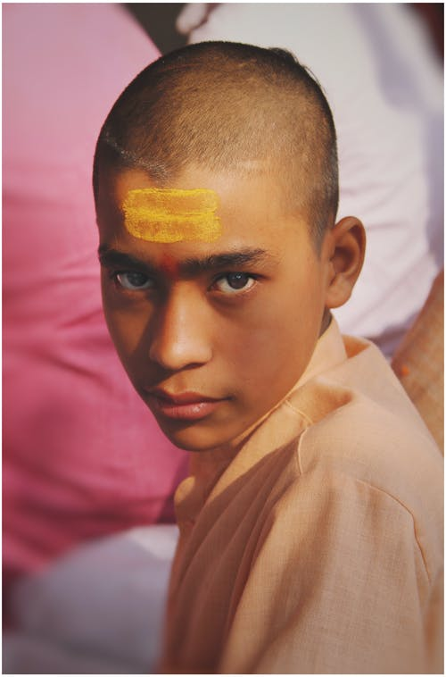 Calm Indian male with short hair and yellow painted stripes on forehead wearing traditional clothes looking at camera on blurred background