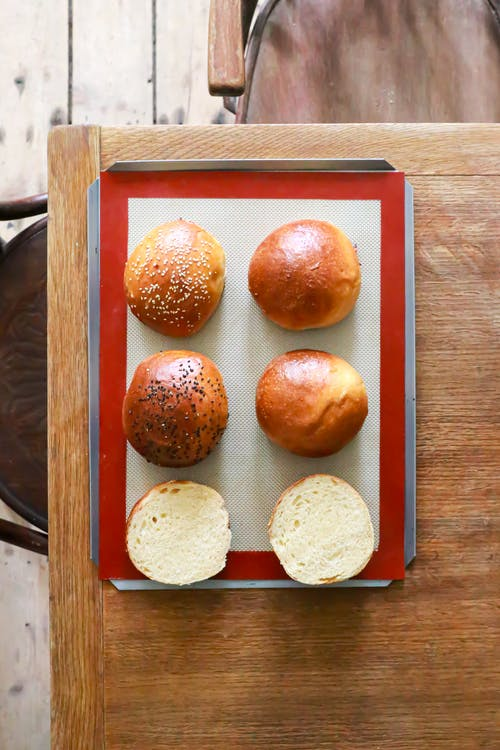 Top view of metal tray with appetizing freshly baked buns with sesame and poppy seeds placed on wooden table in kitchen