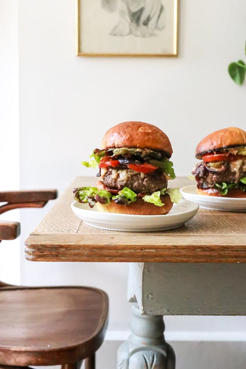 Delicious burgers with beef and veggies served on table