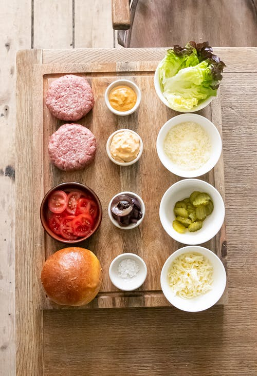 Ingredients for burger placed on wooden table