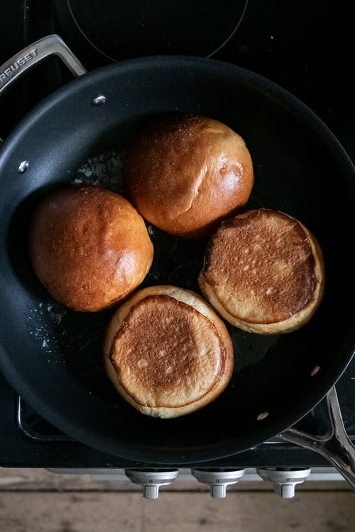 From above of fresh buns for burger frying on hot pan on stove in daytime