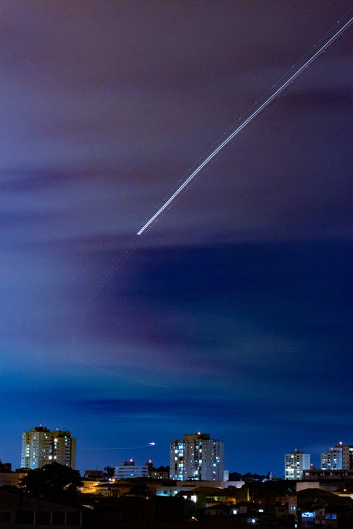Bright shiny trail of plane flight above city with luminous tall buildings at late night under dark blue cloudy sky