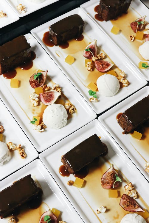Plates with ice cream near figs and chocolate cakes
