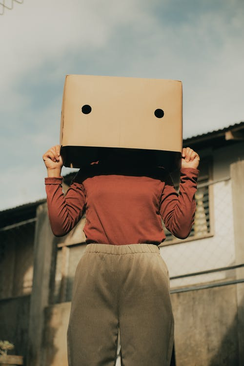 Anonymous woman with box on head near building