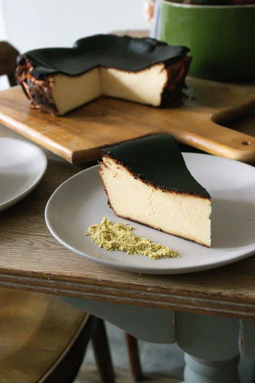 Basque burnt cheesecake on plate and cutting board on table