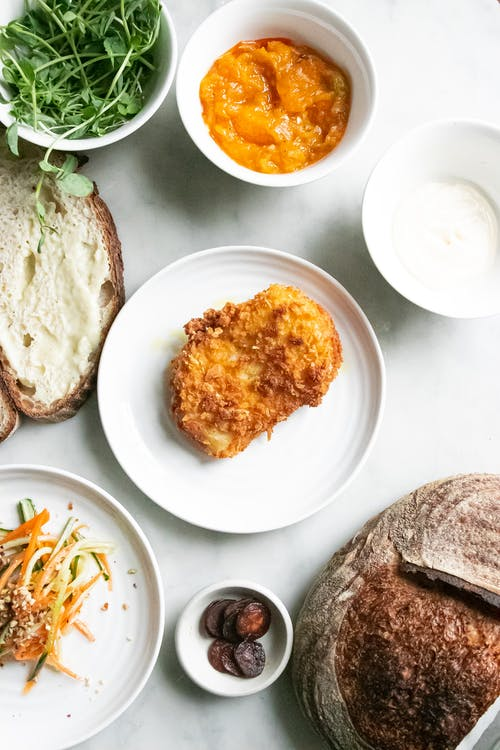 Top view of fried meat on plate near salad with vegetables near bowl with herbs and bread slice with butter near sauce in bowl on table in light place