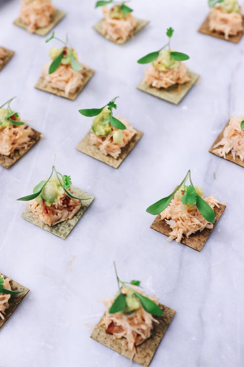 Fish appetizers with herbs on crackers on table