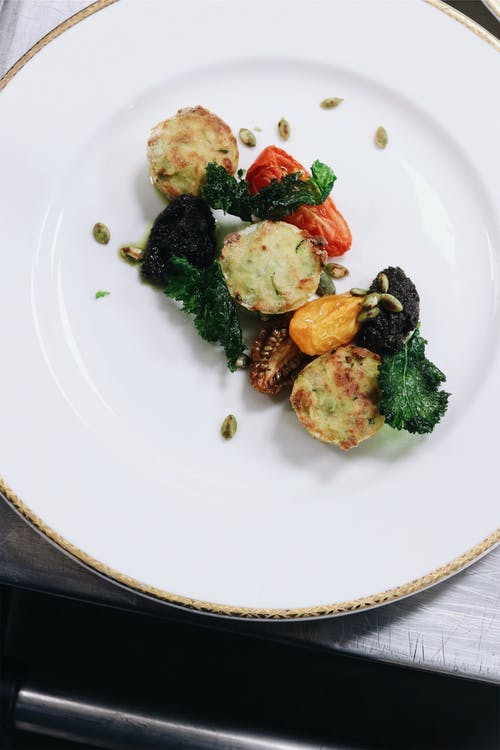 From above of white ceramic plate with vegetarian meatballs with grilled tomatoes and green salad leaves decorated with seeds on table in light restaurant