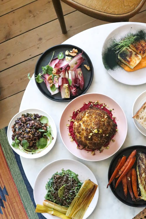 Top view of plates with whole roasted cauliflower near pickled stems with herbs and buckwheat porridge near beans and cutted radichio salad near grilled carrot with corn cob on table