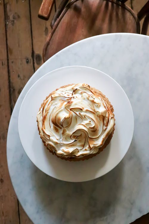 Top view of delicious pie with meringue on plate placed on round white table near chair on wooden floor in light place