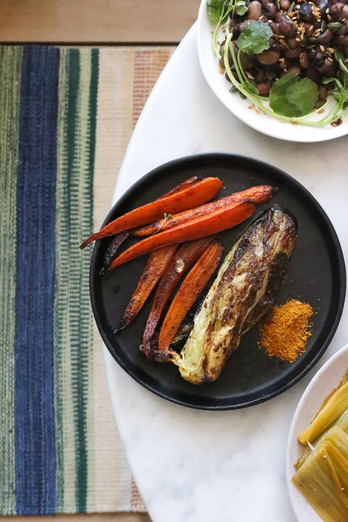 Delicious grilled carrot with corn cob in plate on table