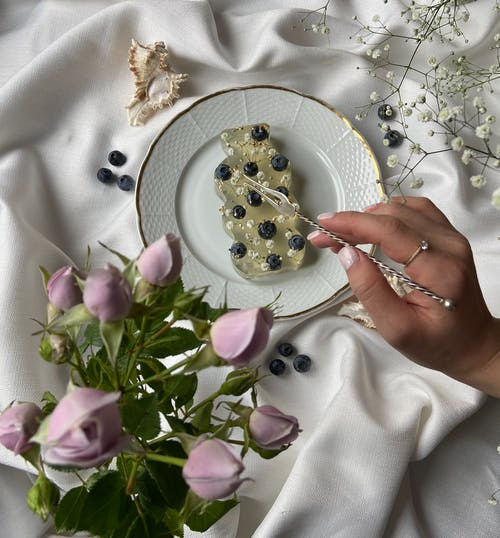 From above of unrecognizable female with fork near ECO soap decorated with blueberries  placed on plate near bouquet of flowers on elegant white fabric