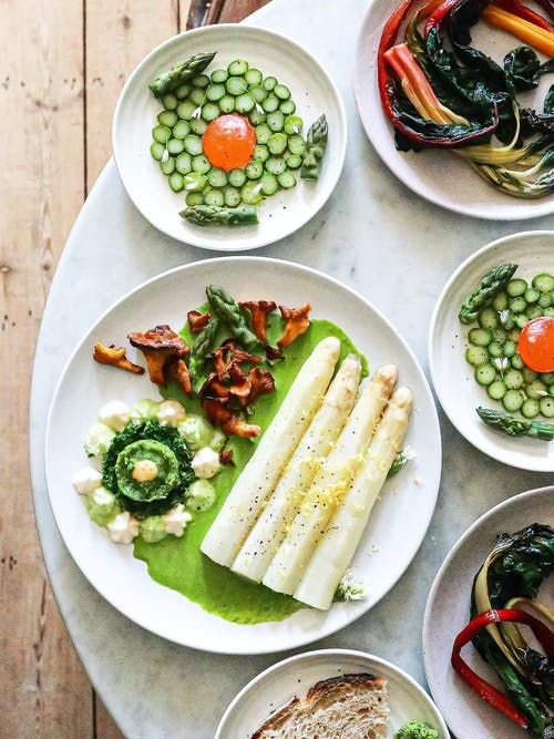 White asparagus with sauce near vegetarian dishes with herbs