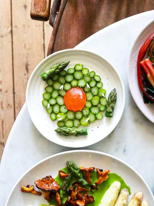 Top view of dish with fresh cut cucumber and yolk served with green asparagus on table near plates of food