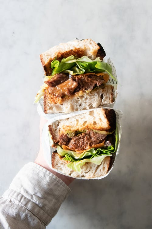 Top view of unrecognizable person with delicious sub sandwich with meat and lettuce cut in half in hand on marble table