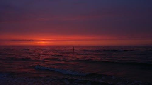 Wavy sea under bright sky at dusk