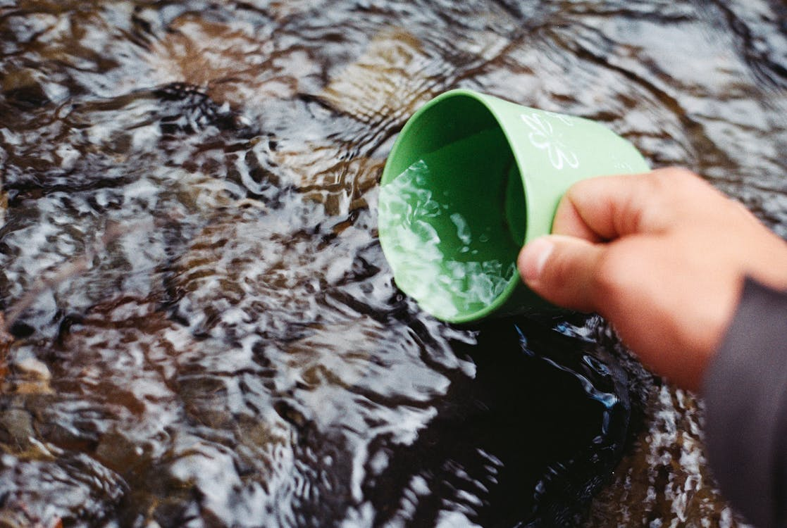 Person Scooping Water Using Green Cup