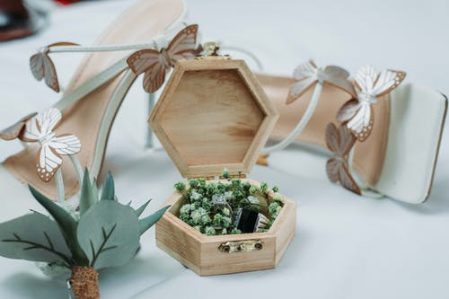 Composition of stylish wedding rings in creative wooden box placed on table near white trendy high heeled shoes