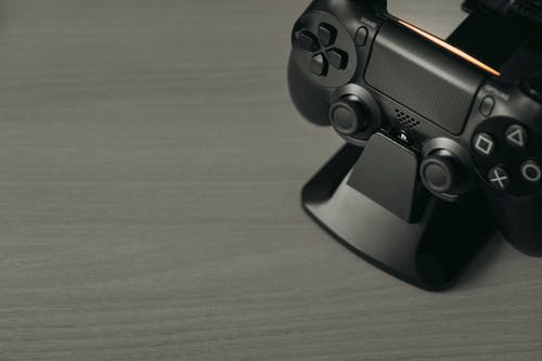 Black Game Controller on Brown Wooden Table