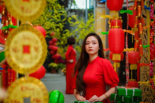Woman in Red Long Sleeve Shirt Standing Near Green and Yellow Balloons