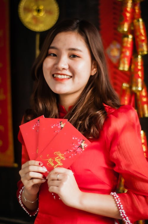 Smiling Woman in Red Long Sleeve Shirt Holding Pink Paper
