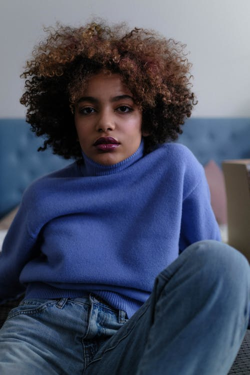 A Woman Wearing a Blue Sweater and Denim Jeans
