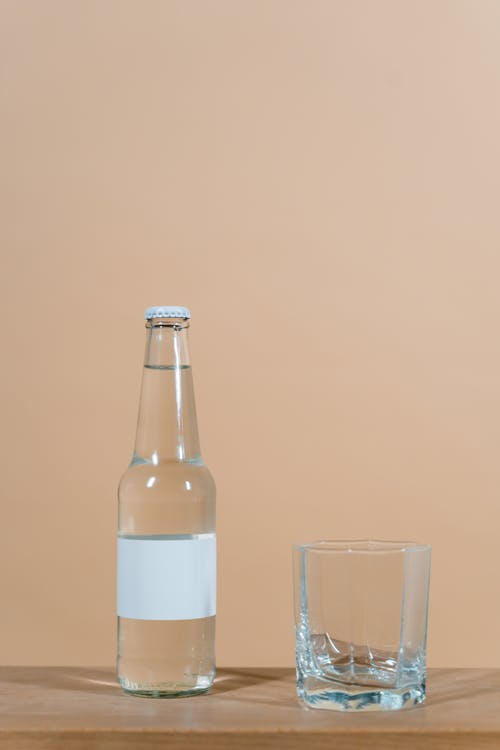 White Labeled Bottle Beside Clear Drinking Glass