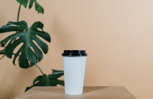 White and Black Plastic Cup on Brown Wooden Table