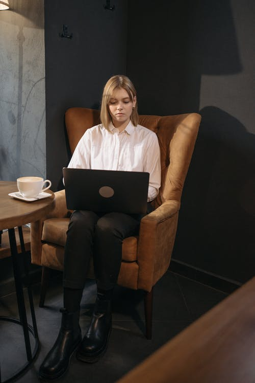 Woman in White Shirt Sitting on Brown Sofa Chair Using Macbook