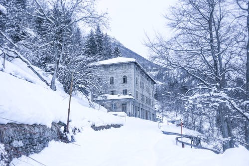 Low angle of aged stone residential building and leafless trees on slope of mountain covered with snow and coniferous forest against cloudy sky