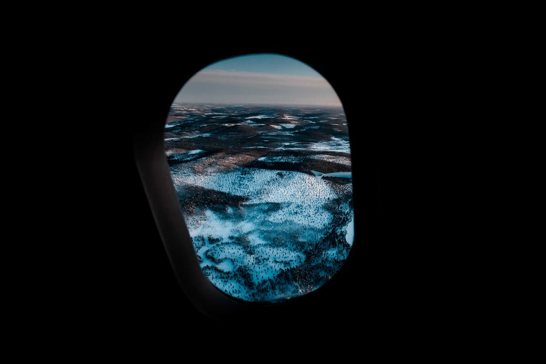Through aircraft window of picturesque mountainous valley covered with snow under cloudy sunset sky