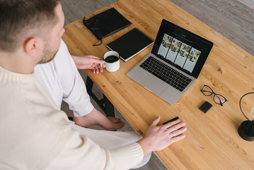 Man in White Long Sleeve Shirt Sitting on Chair in Front of Macbook Pro