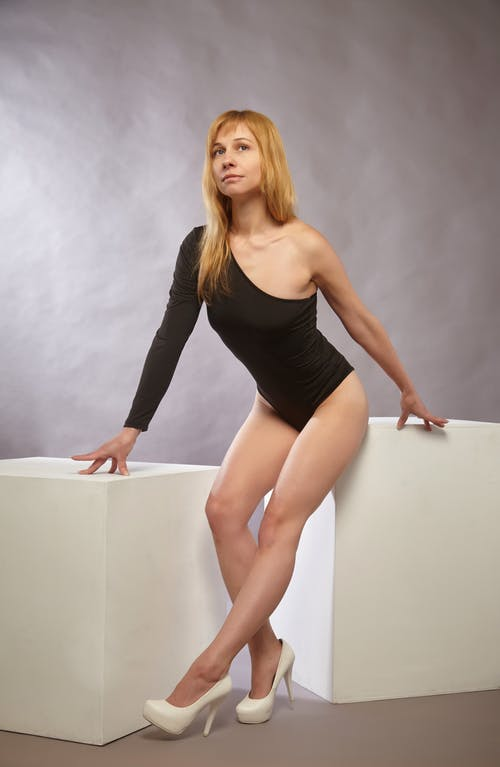 Full body of gorgeous young female model with long blond hair in black bodysuit leaning on white cubes in studio and looking away against gray background