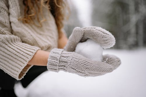 Close-Up Photo of a Person with Knitted Gloves Forming a Snowball